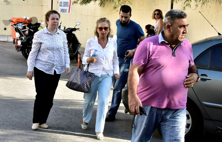Turkish journalist Nazli Ilicak (C), a well-known commentator and former parliamentarian, is escorted by a police officer (R)