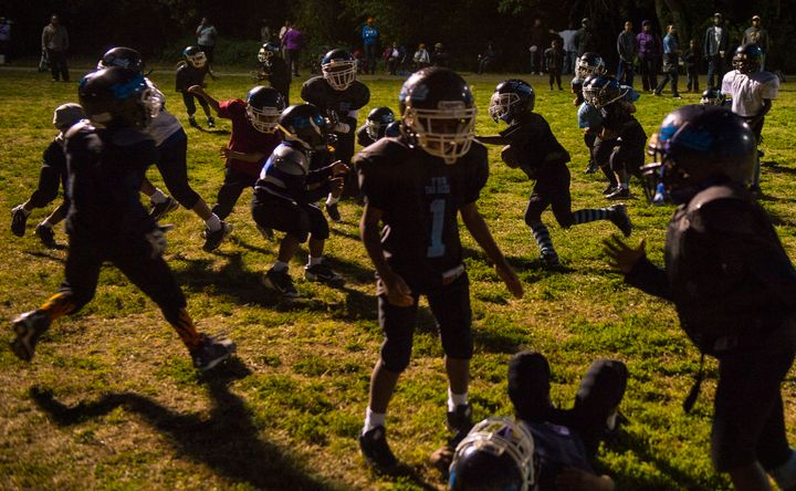 Young D.C. Pop Warner League football players run plays during practice after a visit from former NFL player Cato June, who s