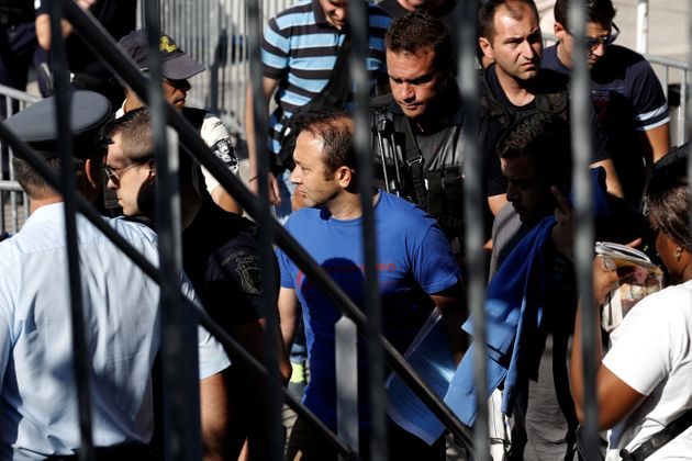 One of the Turkish soldiers who fled to Greece (C) is escorted by special police forces after the postponement...