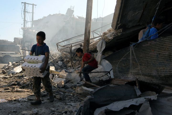 Boys salvage goods from a site hit by airstrikes in the rebel held town of Atareb in Aleppo province on Monday.