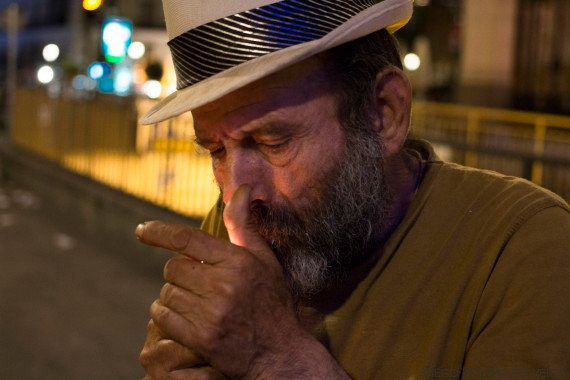 Papi lights a cigarette late at night.