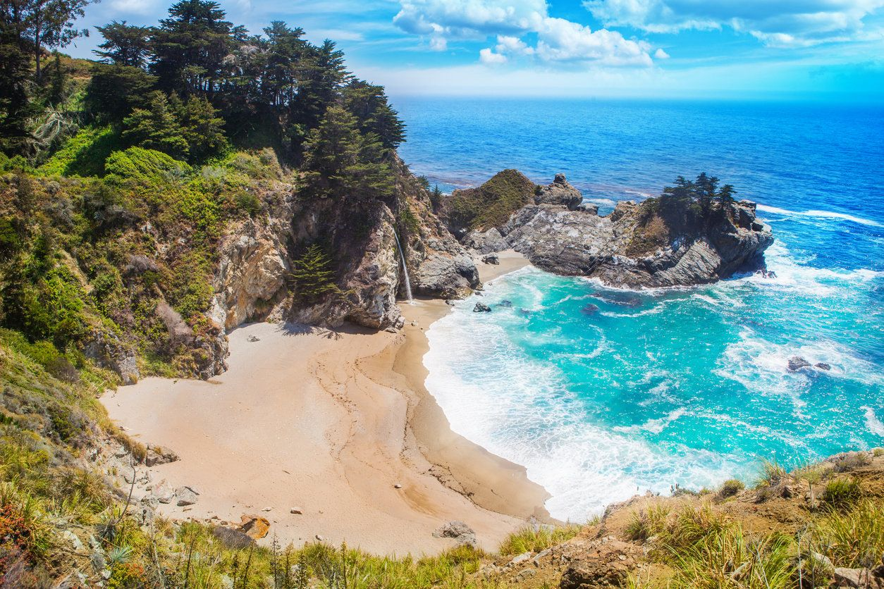 Beautiful photo of the beach with Pfeiffer Falls in Pfeiffer Big Sur State Park California USA on a sunny summer afternoon.
