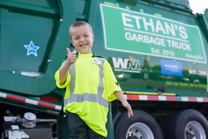 Ethan in front of his garbage truck.