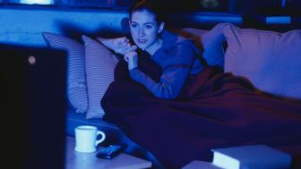 Young woman lying under blanket on sofa, watching television