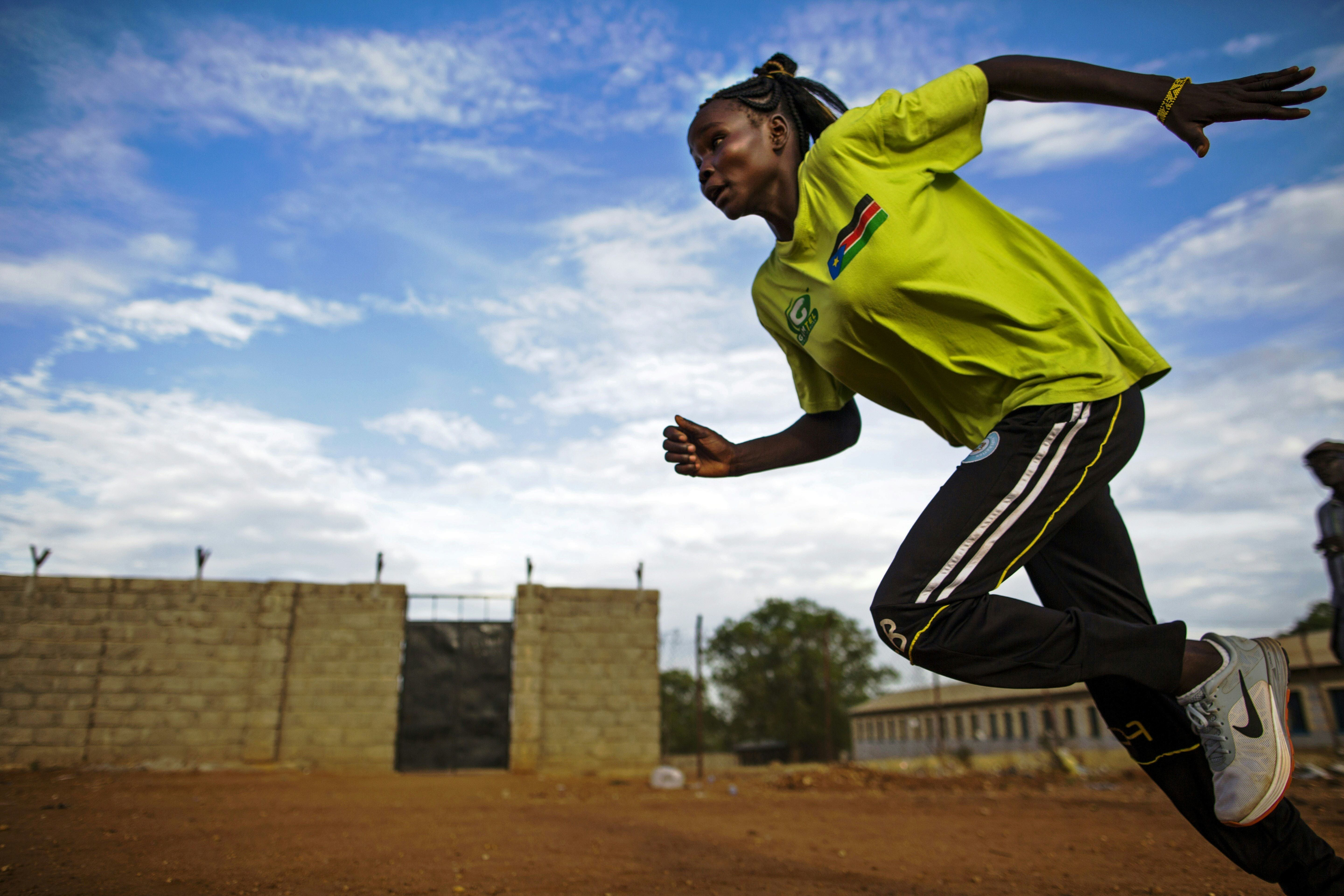 Margret Rumat Rumar Hassan, 19 years old, from Wau, South Sudan, trains at the open field of the Buluk Athletics Track in Juba, South Sudan, on March 18, 2016.  Margret is currently training to be qualified for the Summer Olympic Games in Rio de Janeiro 2016 in the 200 metre and 400 metre events. Margret has already taken part in the Summer Youth Olympic Games in Nanjing, China, in 2014, as independent athlete. Since the South Sudan National Olympic Committee (NOC) was admitted by the International Olympic Committee (IOC) at the 128th IOC Session on 2 August 2015, this is the first time the country will be able to send its first athletes to the competition. Margret, who wants to become a teacher in the future, is still attending primary school because she missed more than 4 years education while she was displaced with her family during the war with Sudan. With five other brothers and sisters, Margret is struggling to convince her mother to go to the Olympics because she would like her to remain at home. AFP PHOTO / ALBERT GONZALEZ FARRAN / AFP / ALBERT GONZALEZ FARRAN        (Photo credit should read ALBERT GONZALEZ FARRAN/AFP/Getty Images)