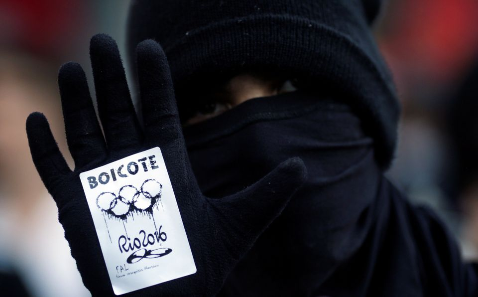 "An anti-government demonstrator, with a sticker which reads ""boycott"" on his hand, attends a protest on the Rio de Janeiro st"