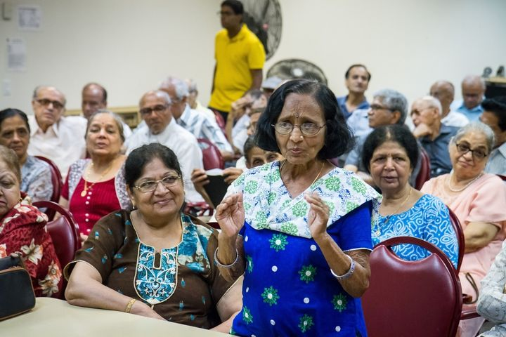 Seniors at India Home's satellite center at Sunnyside Community Services in Queens, New York, look on as Kamuben Chavda speak