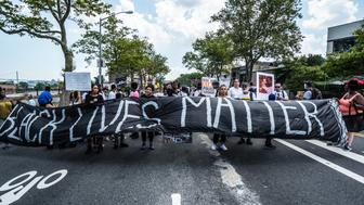 STATEN ISLAND, NEW YORK, NY, UNITED STATES - 2016/07/17: Rally participants hold signs near the site of Eric Garner's death. On the second anniversary of the death of Eric Garner during his attempted arrest by NYPD officer Daniel Pantaleo, Black Lives Matter coalition members and supporters gathered at the site of his death on Bay Street and then marched on to the 120th Precinct of the NYPD intermittently practicing civil disobedience as NYPD Community Affairs officers attempted to regulate the march, in Tompkinsville, Staten Island. (Photo by Albin Lohr-Jones/Pacific Press/LightRocket via Getty Images)