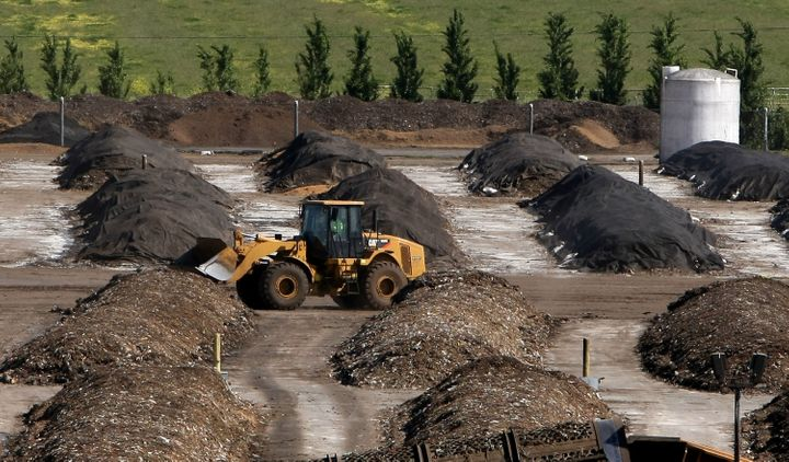 A tractor drives past piles of compost at a compost facility on April 20, 2009, in Vacaville, California.