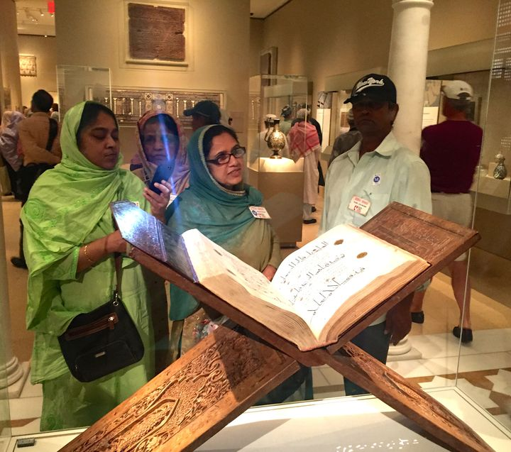 Bangladeshi seniors from the Desi Senior Center in Jamaica, NY, admire an ancient Koran on a visit to the Metropolitan Museum