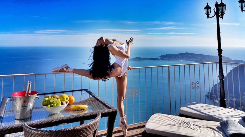 A ballerina in the sky of Eze, France. The peninsula Cap Ferrat lingers in the back