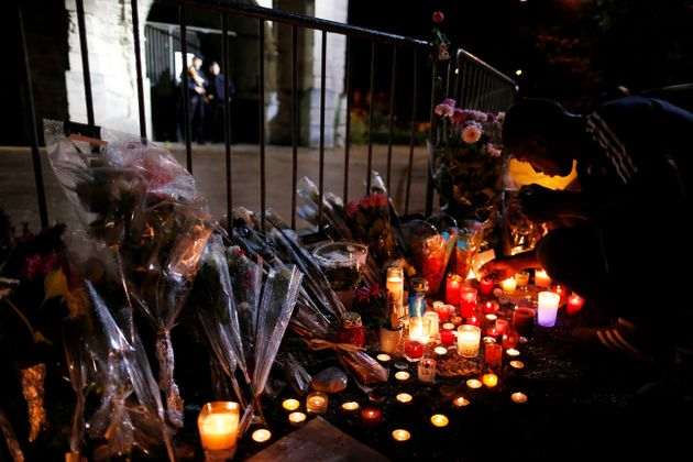 A man lights a candles at a makeshift memorial in front of the Saint-Etienne du Rouvray church in Normandy...