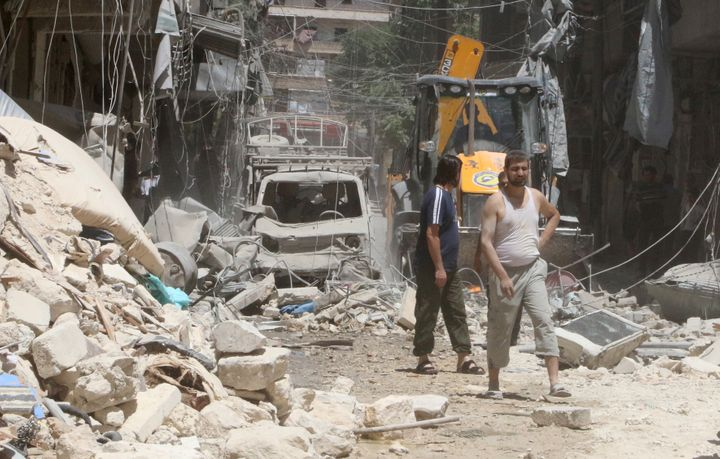 Residents inspect a damaged site after an airstrike on Aleppo's rebel held Al-Mashad neighbourhood, Syria July 26, 2016.