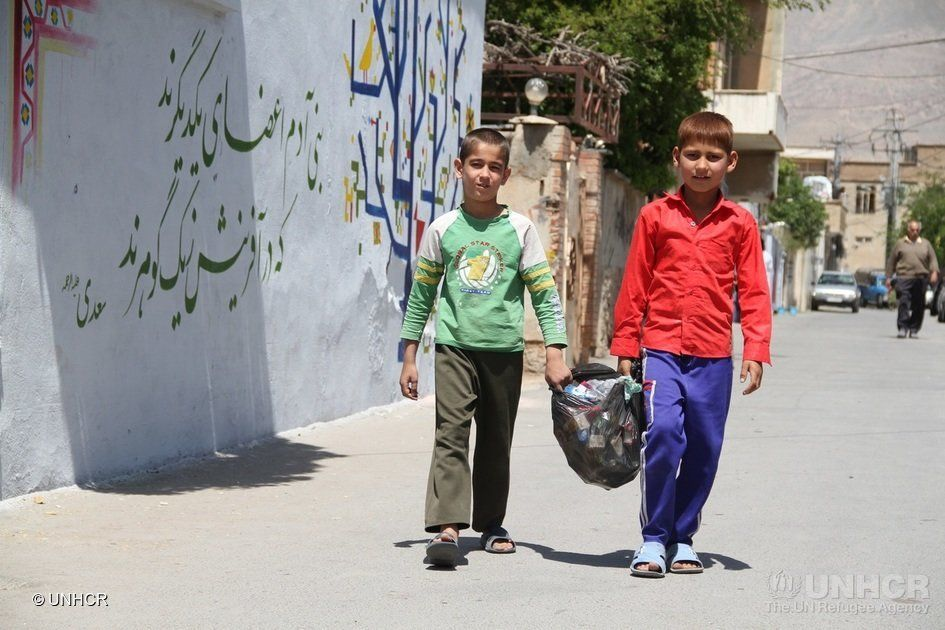 Iranian and Afghan children clean up the neighborhood as part of a week-long community-led mural painting project in Shiraz,