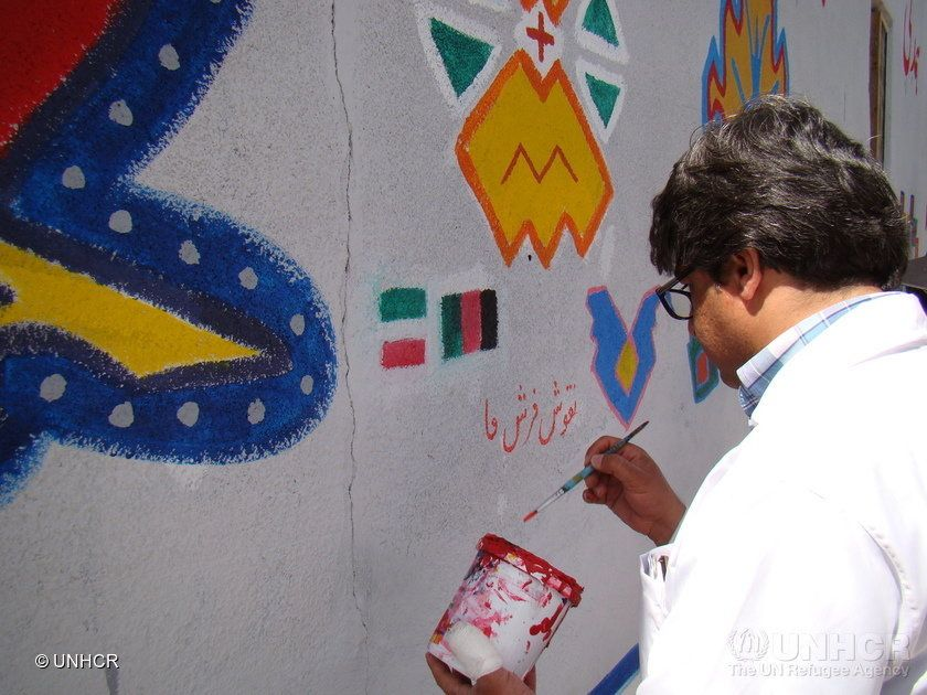 Volunteers paint as part of a week-long community-led mural painting project.