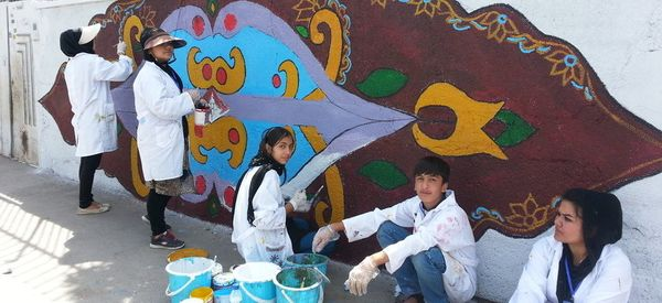 Iranians And Afghan Refugees Work Together To Transform Hateful Graffiti Into Artwork