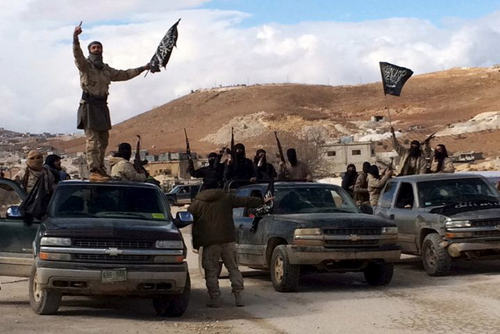 Al Qaeda-linked Nusra Front fighters carry weapons on the back of pick-up trucks in Arsal, eastern Bekaa Valley, Lebanon, Dec