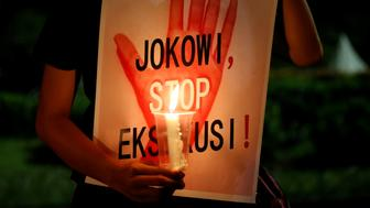 """A protester holds a placard reading """"Jokowi, stop executions"""" during a demonstration against Indonesia's decision to execute 14 drug convicts in front of the Presidential Palace in Jakarta, Indonesia, July 28, 2016. REUTERS/Beawiharta"""