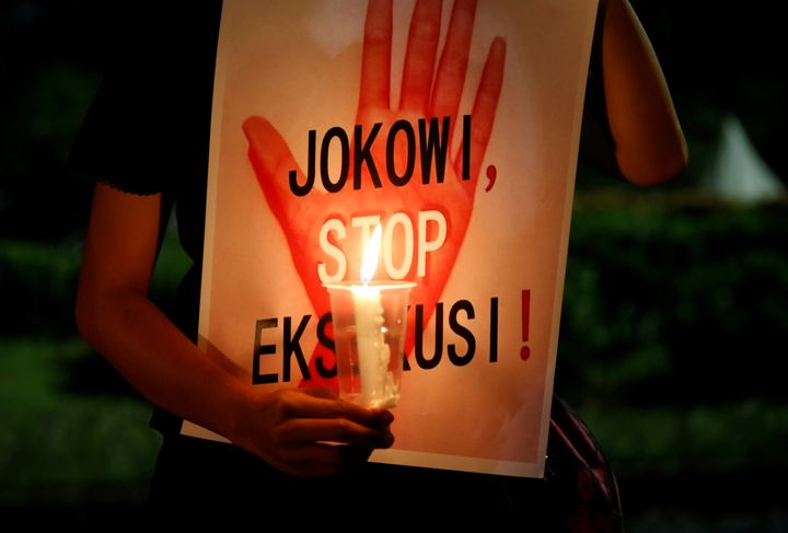 "A protester in Jakarta, Indonesia, holds a placard reading, ""Jokowi, stop executions,"" during a demonstration against th"