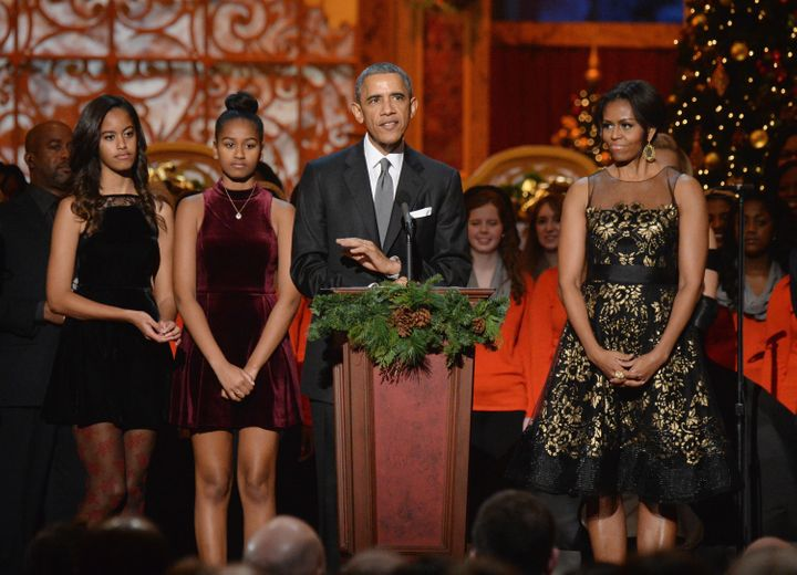 (L-R) Malia Obama, Sasha Obama, President Barack Obama, and First Lady Michelle Obama speak onstage at TNT Christmas in Washi