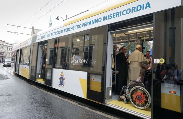 Pope Francis greets a group Catholics with developmental disabilities as he rides with them aboard a city tram to B