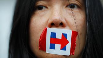 A former Bernie Sanders delegate wears a Hillary Clinton presidential campaign sticker over her mouth as she protests during the third session at the Democratic National Convention in Philadelphia, Pennsylvania, U.S. July 27, 2016. REUTERS/Carlos Barria