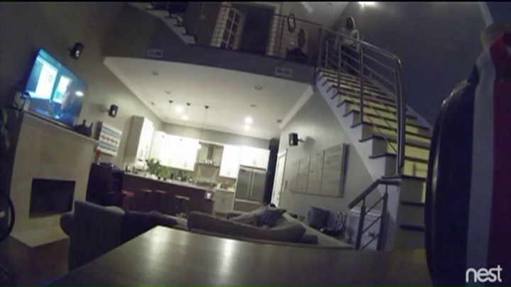 Surveillance video taken early Monday morning shows a man standing on the staircase as the couple sleeps on a couch below.