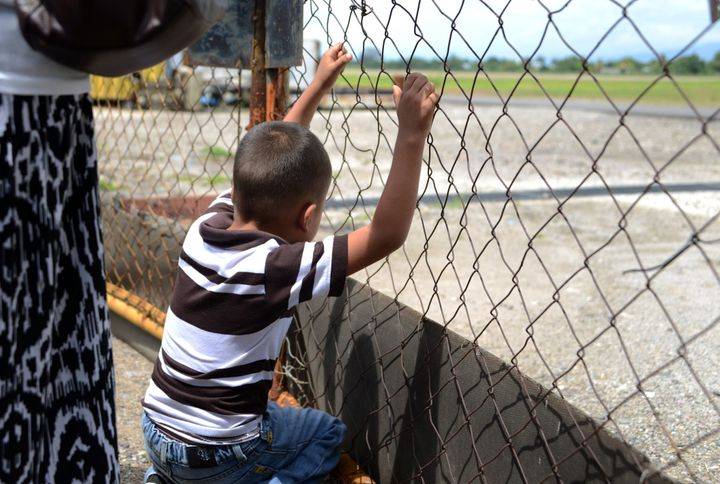 A boy watches as a plane carrying deportees from the United States landsinSan Pedro Sula, Honduras. Clinton's com