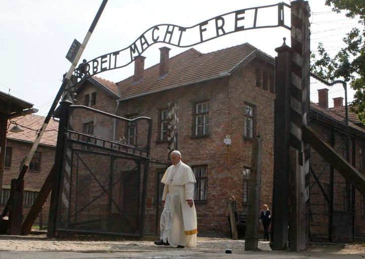 """Pope Francis walks through a gate with the words """"Arbeit macht frei"""" (Work sets you free) at the former Nazi German concentra"""