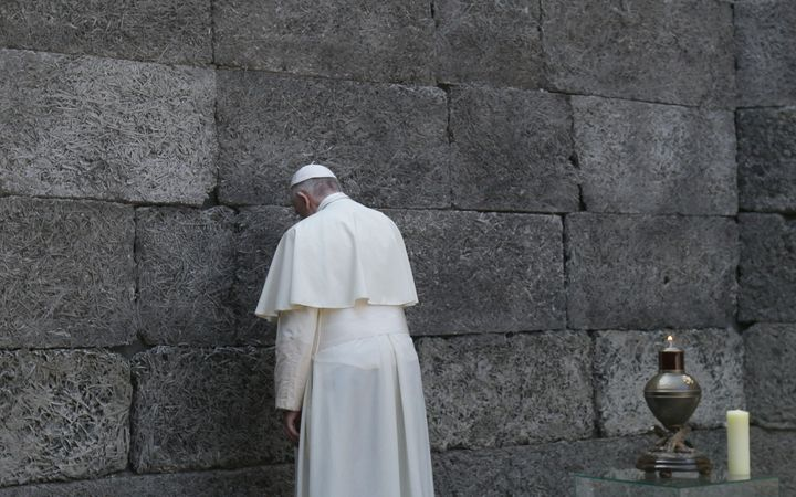 Pope Francis pays respects by the death wall in the former Nazi German concentration and extermination camp Auschwitz-Birkena