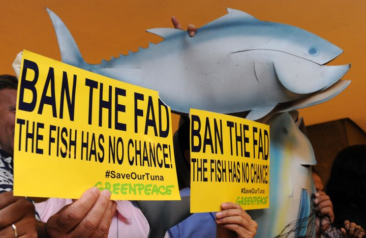 Greenpeace activists holding mock tuna and placards.