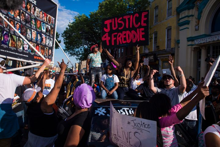 Protesters shout and chant while marching in solidarity with Freddie Gray after it was announced that criminal charges would