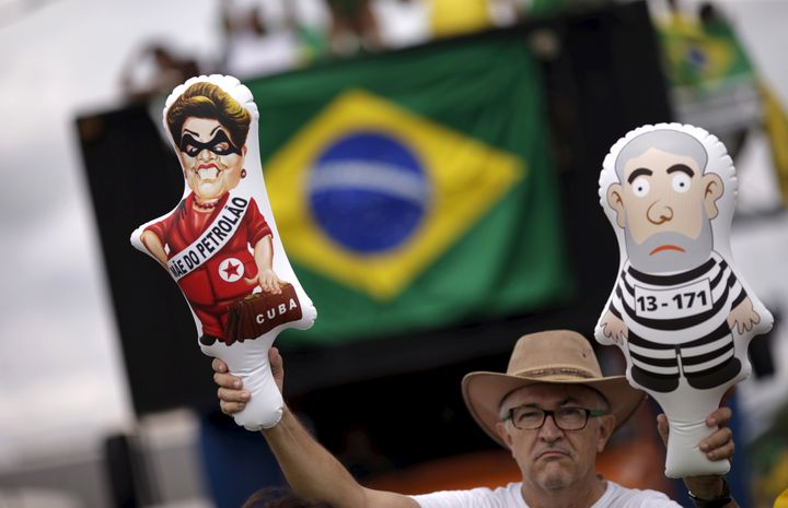 A demonstrator holds inflatable dolls depicting Brazil's former presidents Luiz Inacio Lula da Silva (R) and Dilma Rousseff a