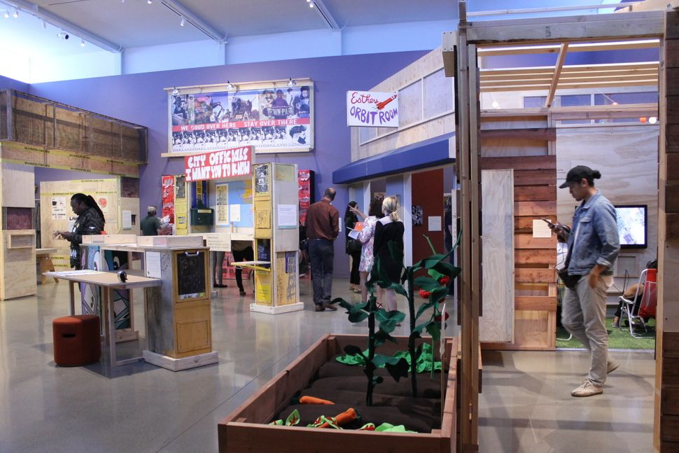 """Installation shot of """"Oakland, I want you to know..."""" In the foreground is the community garden installation, wit"""