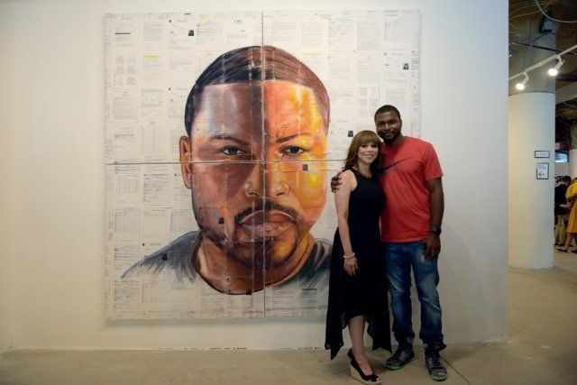 Russell Craig, who was in and out of the system for 12 years, stands beside actress Rosie Perez in front of his artwork displ