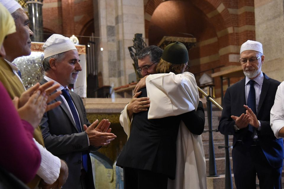 A member of the Muslim community embraces Don Paolo Croci during a Mass in the Catholic church of Santa Maria of Caravaggio i