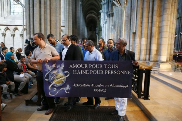 "Men from the Ahmadiyya Muslim Association hold a banner reading ""Love for all, hatred for no one"" during a Mass in Rouen Cath"
