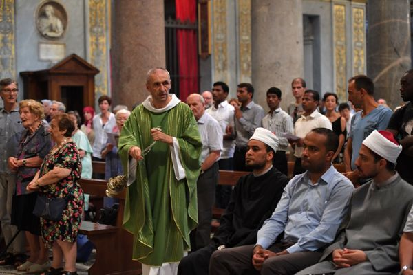 A priest swings incense burner as Muslims take part in a Mass in Santa Maria in Trastevere church in Rome.