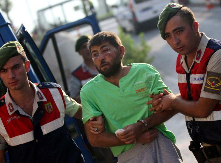 Turkish gendarmeries escort one of the 11 fugitive commandos who were involved in a bid to seize President Tayyip Erdogan dur