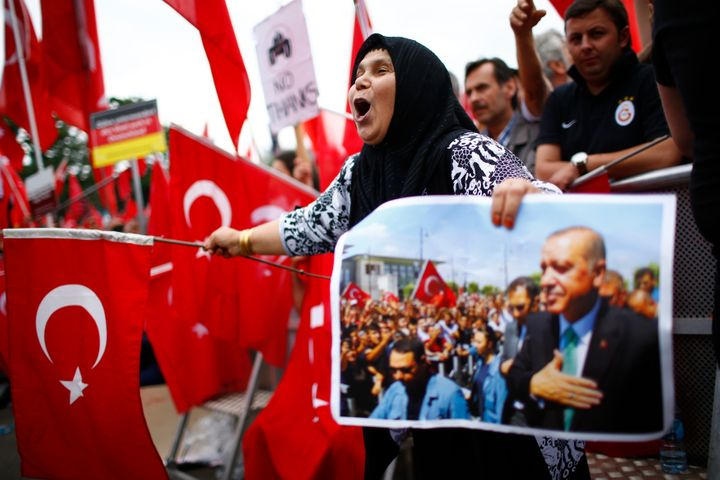 Supporters of Turkish President Tayyip Erdogan wave Turkish flags during a pro-government protest in Cologne, Germany on Sund