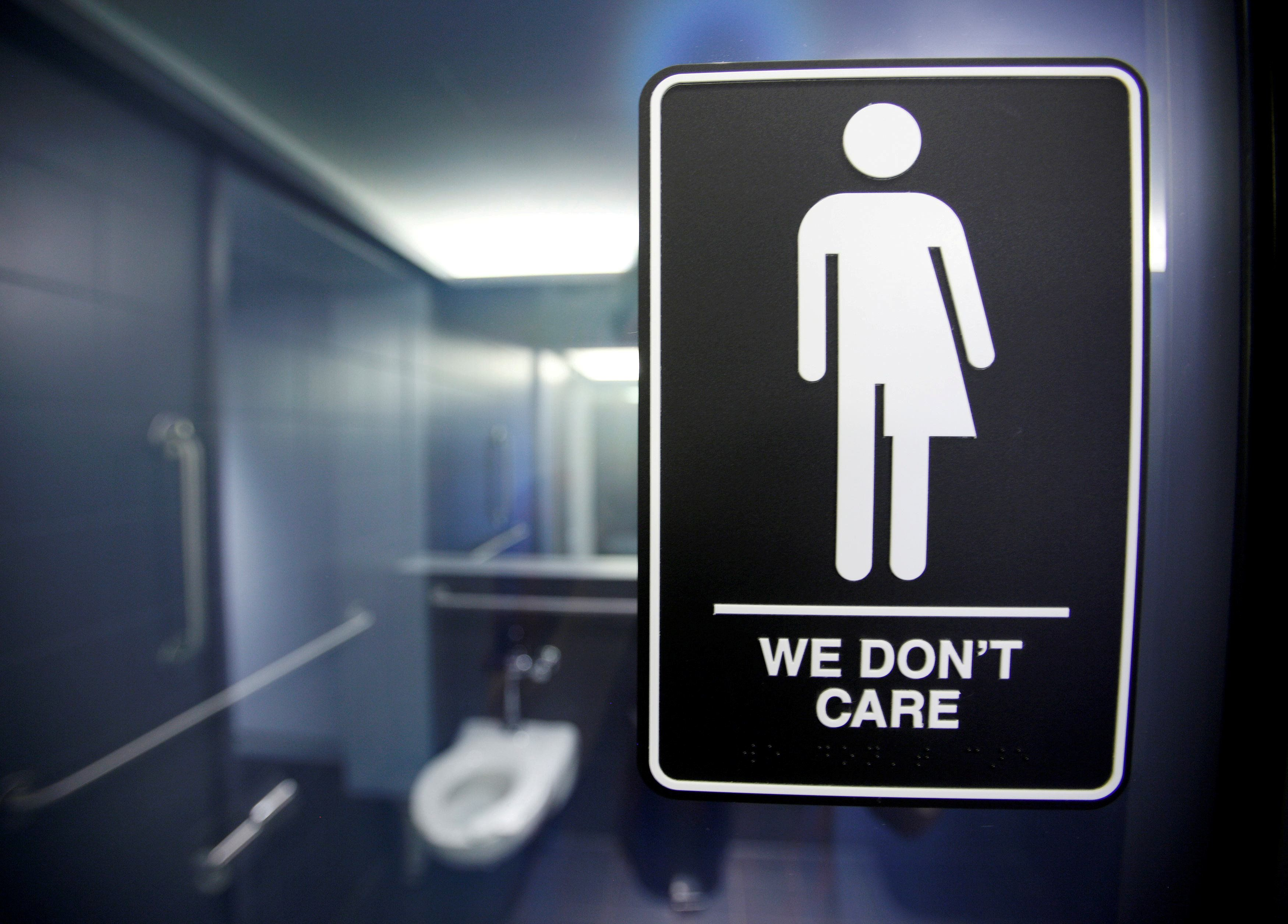 A sign protesting a recent North Carolina law restricting transgender bathroom access is seen in the bathroom stalls at the 2