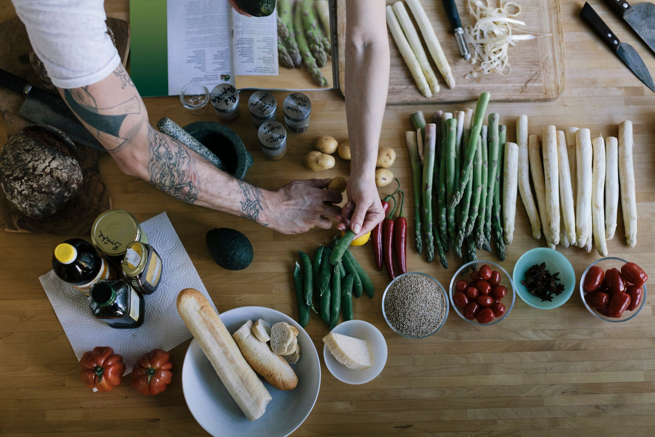 Overhead view of couple preparing food before cooking it. The view shows white and green asparagus plus other items.