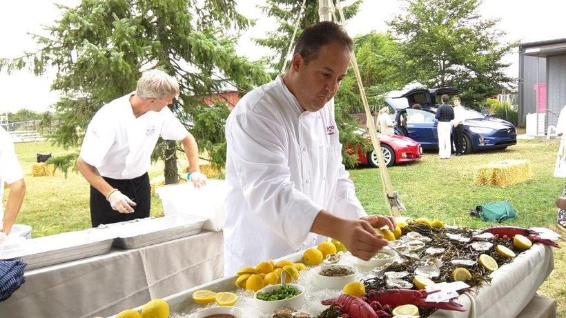 Chefs prepare hors d'oeuvres served outdoors