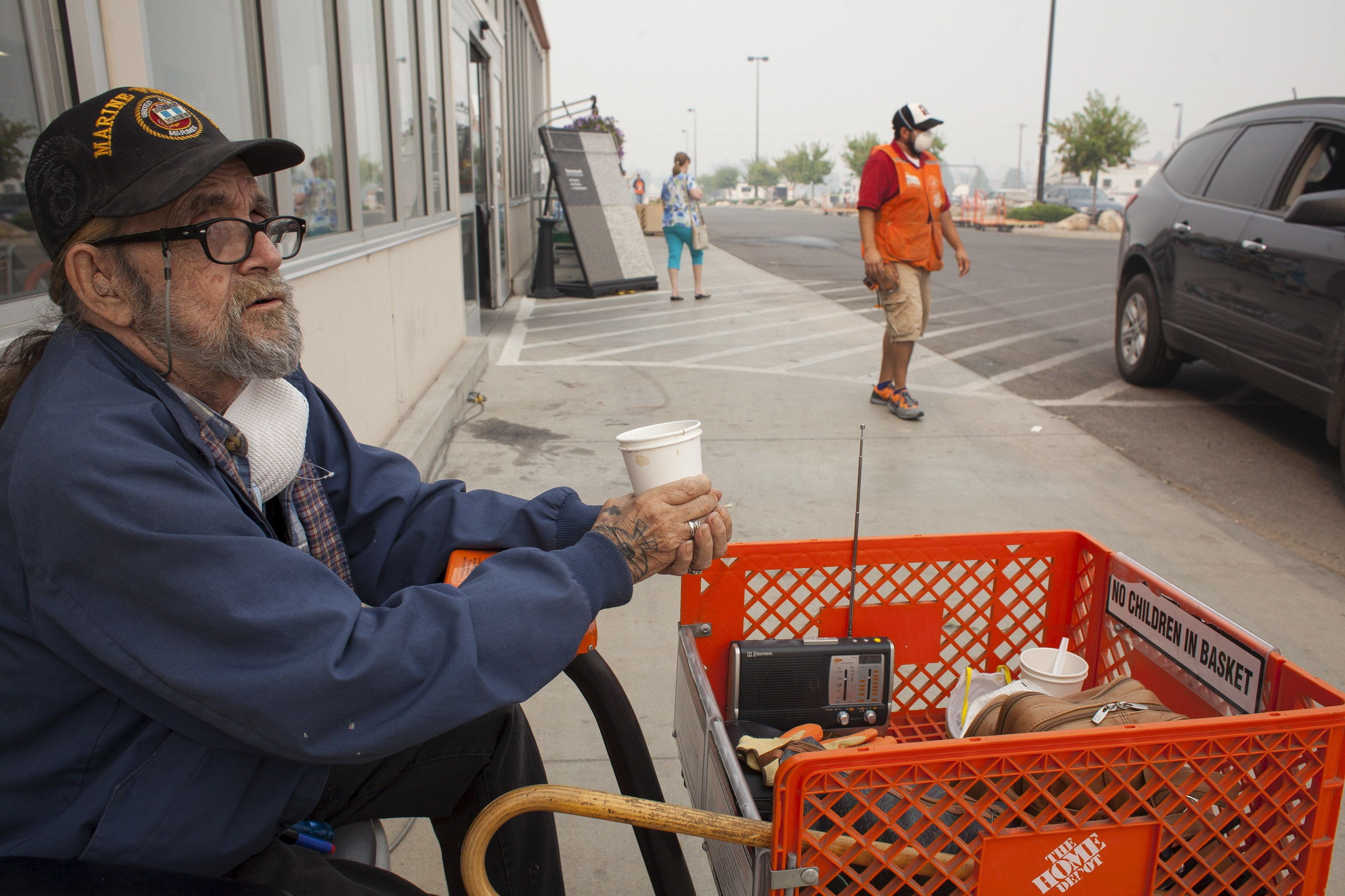 U.S. Marine Corps veteran Martin Silverhawk sits outside a Home Depot store, where he has been living since evacuating his ho