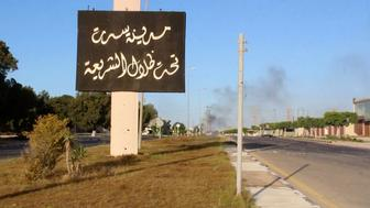 """REFILE - QUALITY REPEATA sign which reads in Arabic, """"The city of Sirte, under the shadow of Sharia"""" is seen as smoke rises in the background while forces aligned with Libya's new unity government advance on the eastern and southern outskirts of the Islamic State stronghold of Sirte, in this still image taken from video on June 9, 2016. via Reuters TV     TPX IMAGES OF THE DAY"""