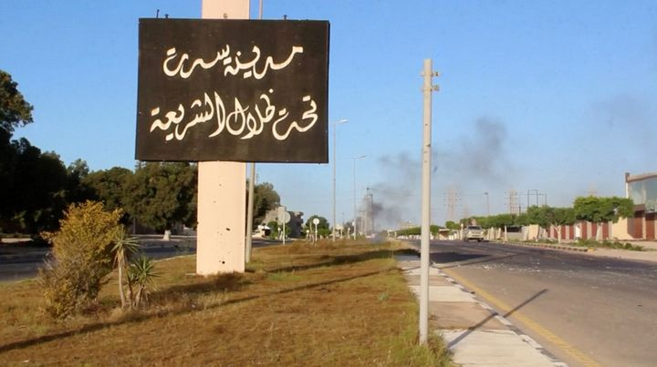 """A sign which reads in Arabic, """"The city of Sirte, under the shadow of Sharia"""" is seen as smoke rises in the background in Jun"""
