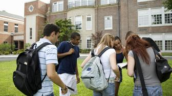Group of students discussing outside school building