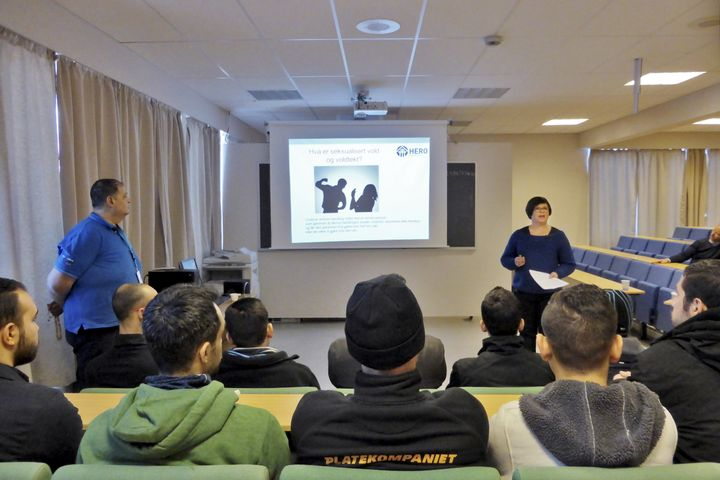 Translator Callas Moustapha (L) looks on as teacher Linda Hagen delivers a lecture to Syrian asylum seekers at a one-day cour