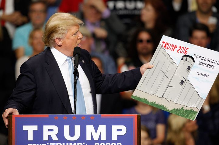 Donald Trump holds a sign supporting his plan to build a wall between the United States and Mexico that he borrowed from a me