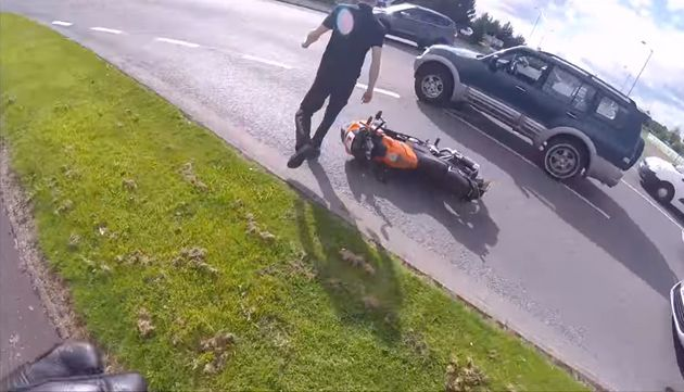 The motorist walks back to his vehicle after shoving the motorcyclist to the
